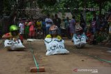 Peserta saat mengikuti lomba balap karung dengan memakai helm ala Formula 1 di Dusun Banjarsari, Desa Bareng, Kabupaten Jombang, Jawa Timur, Sabtu (17/8/2019). Para peserta yang mengikuti lomba balap karung dalam rangkah peringatan hari Kemerdekaan Indonesia ini diharuskan memakai helm, dan peserta harus mencapai garis finish dengan cara ngesot tidak boleh berjalan atau lompat. Antara Jatim/Syaiful Arif/zk