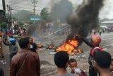 Massa membakar ban saat kerusuhan di pintu masuk Jl. Trikora Wosi Manokwari, Senin (19/8/2019). Aksi ini merupakan buntut dari kemarahan mereka atas peristiwa yang dialami mahasiswa asal Papua di Surabaya, Malang dan Semarang. ANTARA FOTO/Toyiban/nym.