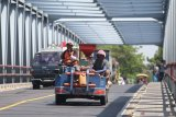 Pekerja mengendarai mesin penggilingan gabah keliling melewati jembatan Kertosono, Nganjuk, Jawa Timur, Selasa (20/8/2019). Mesin penggilingan gabah keliling banyak terlihat di jalan-jalan protokol di daerah tersebut dengan tidak memperdulikan faktor keamanan karena tidak memenuhi syarat untuk dikendarai di jalan raya. Antara Jatim/Prasetia Fauzani/zk.