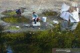 Warga mencuci pakaian menggunakan aliran air yang tercemar limbah di Bendung Situdam, Barugbug, Karawang, Jawa Barat, Rabu (21/8/2019). Kondisi aliran air di bendungan tersebut berubah warna menjadi hitam, keruh dan mengeluarkan bau yang diduga akibat limbah industri sehingga merusak ekosistem dan menganggu aktivitas warga di sekitar bendungan. ANTARA JABAR/M Ibnu Chazar/agr