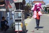 Seorang perajin boneka berjalan kaki membawa boneka berukuran super jumbo menuju toko boneka di Kampung Boneka, Cikampek Utara, Karawang, Jawa Barat, Rabu (21/8/2019). Kampung boneka atau sentra produksi boneka memiliki sekitar 300 perajin boneka yang dapat memproduksi 3000 hingga 5000 boneka per bulan dengan harga jual Rp2.500 - Rp450.000 per boneka tergantung ukuran. Kampung boneka tersebut juga masuk dalam salah satu nominasi kategori destinasi belanja terpopuler Anugerah Pesona Indonesia 2019. ANTARA JABAR/M Ibnu Chazar/agr