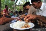 Sejumlah warga bersiap menyantap makanan saat kenduri jeurat (Kenduri Kuburan) di Tempat Pemakaman Umum ( TPU) Desa Alue Raya, Kecamatan Samatiga, Aceh Barat, Aceh, Kamis (22/8/2019). Tradisi kenduri kuburan dengan cara yasinan dan berdoa serta memasak dan makan bersama merupakan tradisi masyarakat Aceh secara turun temurun dengan tujuan untuk mendoakan sanak saudaranya yang telah meninggal dunia. Antara Aceh/Syifa Yulinnas.