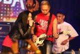 Vokalis band Cokelat Jacklyn Rossy (kiri) bersama gitaris band Cokelat Edwin Marshal Syarif (kedua kanan) melantunkan lagu Anak Garuda saat peluncuran produksi film dan original soundtrack (OST) ANAK GARUDA di Surabaya, Jawa Timur, Sabtu (7/9/2019). Film ANAK GARUDA bercerita tentang tujuh alumni Sekolah Selamat Pagi Indonesia (SPI) yang berhasil bangkit dari keterpurukan dan akhirnya mampu mengelola divisi usaha di sekolah SPI. Antara Jatim/Didik Suhartono/ZK