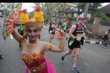 Sejumlah peserta berlari di samping penari bali saat mengikuti Maybank Bali Marathon 2019 di kawasan Gianyar, Bali, Minggu (8/9/2019). Sebanyak 11.659 pelari dari 50 negara seperti Kenya, Australia, Amerika Serikat, Jepang dan Malaysia mengikuti Maybank Bali Marathon 2019 yang diselenggarakan dengan melintasi wilayah Kabupaten Gianyar dan Kabupaten Klungkung. ANTARA FOTO/Fikri Yusuf/nym.