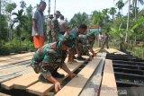 Sejumlah Prajurit TNI Kodim 0105/Aceh Barat bersama warga memperbaiki jembatan penghubung Desa Ujong Raya dan Desa Atong Kecamatan Panton Reu, Aceh Barat, Aceh, Jumat (13/9/2019). Kegiatan karya bakti yang digelar TNI Kodim 0105/Aceh Barat bersama masyarakat di daerah terpencil tersebut dalam rangka memperingati HUT TNI ke-74 sekaligus untuk membangkitkan kembali kearifan lokal budaya gotong royong dengan cara memperbaiki jembatan dan penimbunan badan jalan sepanjang 500 meter. Antara Aceh/Syifa Yulinnas.