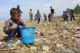 Sejumlah murid Taman Kanak-Kanak (TK) Negeri 2 Meulaboh membersihkan sampah plastik yang mencemari kawasan pantai Desa Peunaga Rayeuk, Meureuboe, Aceh Barat, Aceh, Rabu (18/9/2019). Pembersihan sampah tersebut bertujuan untuk memberikan edukasi sejak dini tentang pentingnya menjaga kebersihan tubuh dan lingkungan. Antara Aceh/Syifa Yulinnas