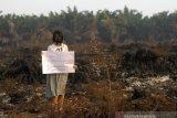 Warga membawa poster bertuliskan keprihatinan kebakaran hutan dan lahan di kawasan Landasan Ulin, Banjarbaru, Kalimantan Selatan, Kamis (19/9/2019).Kota Banjarbaru kini berstatus darurat Kebakaran hutan dan lahan (Karhutla) karena paling terdampak Karhutla dan Satgas Karhutla bersama relawan pemadam kebakaran beserta warga terus berupaya memadamkan Karhutla yang terus meluas di sejumlah daerah Provinsi Kalsel.Foto Antaranews Kalsel/Bayu Pratama S.