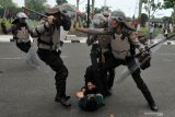 Petugas kepolisian terlibat bentrok dengan mahasiswa saat unjuk rasa menolak RUU KUHP dan UU KPK hasil revisi di Kantor DPRD Jambi, Senin (30/9/2019). Unjuk rasa mahasiswa dan pelajar tersebut berakhir ricuh. ANTARA FOTO/Wahdi Septiawan/foc.