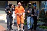 Polisi menggiring warga negara Rusia Andrew Ayer (tengah) dalam konferensi pers pengungkapan kasus peredaran narkotika di Mapolresta Denpasar, Bali, Selasa (8/10/2019). Warga negara Rusia yang berperan sebagai pengedar narkoba lintas negara tersebut ditangkap Satresnarkoba Polresta Denpasar dan Satgas CTOC Polda Bali di kawasan Kuta, Badung pada Selasa (1/10) dengan barang bukti 521,11 gram hasish. ANTARA FOTO/Nyoman Hendra Wibowo/nym.
