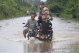 Pengendara memanfaatkan jasa angkut kendaraan roda dua untuk menembus jalan yang terendam banjir di Desa Layung, Bubon, Aceh Barat, Aceh, Rabu (9/10/2019). Warga yang berada di kawasan itu memanfaatkan banjir untuk menyewakan jasa angkut kendaraan melintasi banjir dengan tarif Rp10.000 per sekali angkut kendaraan. Antara Aceh/Syifa Yulinnas.