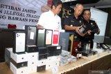 Petugas menunjukkan barang bukti pelaku usaha jasa titipan di Kantor Pengawasan dan Pelayanan Bea dan Cukai (KPPBC) Tipe Madya Pabean Juanda, Sidoarjo, Jawa Timur, Kamis (10/10/2019). antor Pengawasan Dan Pelayanan Bea Dan Cukai Tipe Madya Pabean Juanda mentertibkan pelaku usaha jasa titipan berupa 40 box iPhone, 90 botol MMEA dan 84 hp iPhone 11 yang belum dipasarkan di Indonesia. Antara Jatim/Umarul Faruq/zk