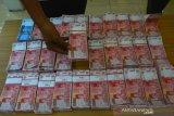 Petugas menunjukkan uang palsu saat rilis di Mapolres Lamongan, Jawa Timur, Kamis (10/10/2019). Sindikat pengedar uang palsu dengan modus dukun pengganda uang berhasil dibongkar Polres Lamongan. Polisi berhasil mengamankan 7 orang pelaku serta upal senilai Rp304 juta. Antara Jatim/Syaiful Arif/ak