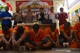 Kapolres Lamongan Feby DP Hutagalung (tengah), Kasat Reskrim AKP Wahyu Normal Hidayat (tiga kanan) saat rilis pengedar uang palsu di Mapolres Lamongan, Jawa Timur, Kamis (10/10/2019). Sindikat pengedar uang palsu dengan modus dukun pengganda uang berhasil dibongkar Polres Lamongan. Polisi berhasil mengamankan 7 orang pelaku serta upal senilai Rp304 juta. Antara Jatim/Syaiful Arif/ak