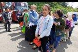 Sejumlah Pekerja Migran Indonesia berbaris untuk menjalani pendataan saat tiba di Pos Lintas Batas Negara (PLBN) Entikong, Kabupaten Sanggau, Kalimantan Barat, Rabu (16/10/2019). KJRI Kuching Sarawak mengawal 53 pekerja migran bermasalah yang dideportasi Malaysia melalui Depot Imigresen Bekenu Miri karena melanggar undang-undang imigrasi di Malaysia ANTARA FOTO/Agus Alfian/nym.