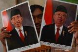 Warga menunjukkan foto Presiden dan Wakil Presiden Republik Indonesia periode 2019-2024, Joko Widodo dan KH Ma'ruf Amin yang akan dipasang bingkai di Jombang, Jawa Timur, Sabtu (19/10/2019). Menjelang pelantikan presiden dan wakil presiden,  sejumlah pedagang mulai menjual bingkai foto Jokowi-Ma'ruf Amin dengan berbagai versi dengan harga Rp50 ribu per pasang. Antara Jatim/Syaiful Arif/zk.