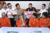 Petugas menunjukkan barang bukti narkotika dan tersangka warga negara Thailand berinisial SM (kanan), KK (kedua kanan), warga negara Rusia TF (kedua kiri) dan warga negara Prancis OJ (kiri) saat rilis di Kantor Bea dan Cukai Ngurah Rai, Bali, Senin (21/10/2019). Bea dan Cukai Ngurah Rai berhasil menggagalkan tiga kasus upaya penyelundupan narkotika ke Bali dan menangkap empat orang tersangka tersebut dengan barang bukti keseluruhan yaitu sabu-sabu seberat 958 gram serta kokain seberat 22,71 gram. ANTARA FOTO/Fikri Yusuf/nym.