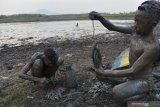 Tiga orang  bocah mencari ikan di sisa lumpur dasar Waduk Saradan yang mengering di Kabupaten Madiun, Jawa Timur, Rabu (30/10/2019). Sejak sekitar seminggu terakhir, waduk yang berada di kawasan hutan Saradan tersebut mengering dan tinggal menyisakan lumpur di dasar waduk. Antara Jatim/Siswowidodo/zk.