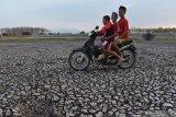 Tiga orang  bocah berboncengan sepeda motor melintas di dasar Waduk Saradan yang mengering di Kabupaten Madiun, Jawa Timur, Rabu (30/10/2019). Sejak sekitar seminggu terakhir, waduk yang berada di kawasan hutan Saradan tersebut mengering dan tinggal menyisakan lumpur di dasar waduk. Antara Jatim/Siswowidodo/zk.