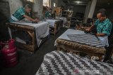 Para pembatik melukis lembaran-lembaran kain bahan mentah batik cap usai diresmikannya Kampung Batik Bright Gas oleh PT Pertamina (persero) Marketing Operation Region III di pusat produksi Agnesha, Kampung Ciroyom, Kota Tasikmalaya, Jawa Barat, Jumat (1/11/2019). Sebanyak 25 perajin di sentra batik Tasikmalaya telah melakukan trade in atau tukar gratis Bright Gas, dengan dua tabung LPG Subsidi tiga kilogram sehingga diharapkan bisa digunakan tepat sasaran untuk masyarakat pra sejahtera dan usaha mikro, dengan konsumsi LPG Non Subsidi di wilayah Priangan Timur, Jabar mencapai 10.016 metrik ton (MT) pada Januari hingga September 2019. ANTARA JABAR/Adeng Bustomi/agr