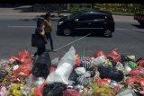 Dua wisatawan melintas di dekat tumpukan sampah di pinggir Jalan Raya Kuta, Badung, Bali, Jumat (8/11/2019). Kawasan pariwisata tersebut kini menghadapi permasalahan sampah yang menumpuk di sejumlah tempat sebagai dampak dari pembatasan pembuangan sampah di TPA Regional Sarbagita Suwung Denpasar dan penutupan tempat pembuangan sampah sementara di Kuta yang diprotes warga. ANTARA FOTO/Nyoman Hendra Wibowo/nym
