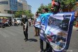 Komunitas Pecinta Kereta Api menunjukkan stiker himbauan saat sosialisasi disiplin berlalu lintas di perlintasan kereta api, di Jalan A Yani, Surabaya, Jawa Timur, Minggu (10/11/2019). Sosialisasi yang digelar PT Kereta Api Indonesia (KAI) Daop 8 Surabaya dengan membagikan stiker himbauan, bendera Merah Putih serta bunga itu bertujuan memberikan pemahaman kepada masyarakat untuk berhati-hati ketika melintas di perlintasan kereta api. Antara Jatim/Didik S/ZK