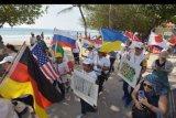Peserta membawa bendera berbagai negara saat mengiringi obor perdamaian pada Parade Peace Run di Kuta, Badung, Bali, Sabtu (16/11/2019). Parade tersebut diikuti 13 negara untuk pertukaran kebudayaan dan berbagi pesan kedamaian, keharmonisan dan persahabatan. ANTARA FOTO/Nyoman Hendra Wibowo/nym.