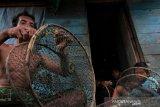Seorang nelayan dibantu dua orang anaknya sedang merakit Rakeng yaitu perangkap kepiting yang terbuat dari bambu dan jala di Kampung Muara Kecil, Kecamatan Muara Jawa, Kabupaten Kutai Kartanegara, Provinsi Kalimantan Timur yang warganya hampir seluruhnya mengandalkan kehidupan pada profesi nelayan.(Foto ANTARA/Suryawan)