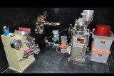 Kepala Loka POM Bogor Muhammad Rusydi Ridha memeriksa salah satu mesin pembuat obat palsu saat menggerebek rumah produksi obat palsu di Gang Pesantren RT 02/07, Kelurahan Kedung Waringin, Tanah Sareal, Kota Bogor, Jawa Barat, Rabu (20/11/2019). Satreskrim Polresta Bogor Kota menggerebek sebuah rumah yang dijadikan tempat produksi obat palsu dan mengamankan dua tersangka serta 11 mesin yang dijadikan alat untuk memproduksi obat palsu tersebut. ANTARA FOTO/Arif Firmansyah/nym