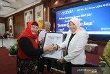 Direktur Keuangan, MSDM dan Umum Perum LKBN Antara Nina Kurnia Dewi (kiri) memberikan penghargaan sang Inspirator perempuan Kalsel kepada Bupati Kabupaten Barito Kuala Normiliyani (kanan) saat acara Penghargaan Perempuan Hebat Kalsel dan Seminar