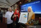 Direktur Keuangan, MSDM dan Umum Perum LKBN Antara Nina Kurnia Dewi (kiri) memberikan penghargaan kepada Perempuan Hebat Kalsel terpilih saat acara Penghargaan Perempuan Hebat Kalsel dan Seminar