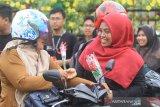 Petugas Kantor Pelayanan Pajak (KPP) Pratama Meulaboh membagikan bunga kepada pengguna jalan saat peringatan Hari Antikorupsi Sedunia (Hakordia) di Meulaboh, Aceh Barat, Aceh, Senin (9/12/2019). Aksi memperingati Hari Antikorupsi Sedunia (Hakordia) tersebut diisi dengan pembagian bunga kepada pengendara sebagai bentuk simpatik dan sosialisasi. Antara Aceh/Syifa Yulinnas)