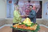 Kepala Biro Antara Jatim Slamet Hadi Purnomo (kanan) memberikan potongan tumpeng kepada mantan Kepala biro ANTARA Jawa Timur Siti Farochah (kiri) saat menghadiri HUT ke 82 LKBN ANTARA di Grha ANTARA Jatim, Surabaya, Jawa Timur, Jumat (13/12/2019). Dalam HUT tersebut Pewarta ANTARA biro Jatim meluncurkan buku karkhas yang berjudul