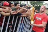 Pesepak bola Bali United Melvin Platje (kanan) menyapa suporter saat mengikuti Parade Juara Liga 1 2019 di kawasan Gianyar, Bali, Senin (23/12/2019). Parade Juara dari kawasan Lapangan Puputan Badung Kota Denpasar menuju Stadion Kapten I Wayan Dipta Kabupaten Gianyar diikuti oleh ribuan pendukung Bali United untuk merayakan keberhasilan tim Bali United menjadi Juara Liga 1 2019. ANTARA FOTO/Fikri Yusuf/nym.