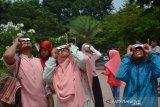 Masyarakat mengamati gerhana matahari sebagian (GMS) menggunakan kacamata khusus di Alun-alun Mojokerto, Jawa Timur, Kamis (26/12/2019). Di wilayah Jawa Timur, gerhana matahari cincin hanya dapat dilihat sebagian atau gerhana matahari sebagian. Antara Jatim/Syaiful Arif/zk