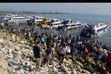 Wisatawan menunggu giliran kapal cepat saat akan menyeberang menuju ke pulau Nusa Penida dan Nusa Lembongan di Pantai Sanur, Denpasar, Bali, Selasa (31/12/2019). Penyeberangan dari Pantai Sanur menuju pulau Nusa Penida dan Nusa Lembongan padat wisatawan karena banyaknya turis yang ingin merayakan pergantian tahun dan liburan di pulau tersebut. ANTARA FOTO/Nyoman Hendra Wibowo/nym