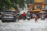 Sejumlah pengendara menorobos genangan air saat banjir melanda kawasan Jalan Brigjen Katamso, Banjarmasin, Kalimantan Selatan, Selasa (31/12/2019). Banjir yang sering melanda kawasan jalan tersebut diakibatkan intensitas hujan yang tinggi serta diperparah sistem drainase yang buruk. Foto Antaranews Kalsel/Bayu Pratama S.
