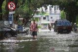 Warga menuntun sepedanya melintasi genangan air saat banjir melanda kawasan Jalan Lambung Mangkurat Banjarmasin, Kalimantan Selatan, Selasa (31/12/2019). Banjir yang sering melanda kawasan jalan tersebut diakibatkan intensitas hujan yang tinggi serta diperparah sistem drainase yang buruk. Foto Antaranews Kalsel/Bayu Pratama S.