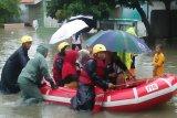 Personel PMI Kota Tangerang, Banten mengevakuasi warga yang terjebak banjir dengan menggunakan perahu karet. (Antara/HO/Humas PMI).