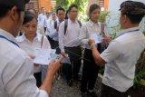 Petugas memeriksa kartu peserta menjelang tes seleksi kompetensi dasar berbasis komputer bagi calon pegawai negeri sipil (CPNS) tingkat Provinsi Bali di Kantor Badan Pengembangan Sumber Daya Manusia (BPSDM) Provinsi Bali, Denpasar, Bali, Selasa (28/1/2020). Seleksi tersebut diikuti 36.193 peserta tingkat provinsi dan empat kabupaten/kota di Bali yang dilaksanakan pada 28 Januari hingga 17 Februari 2020. ANTARA FOTO/Nyoman Hendra Wibowo/nym.