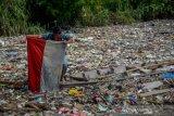 Seorang warga menemukan bendera merah putih di antara sampah plastik di Sungai Citepus yang bermuara ke Sungai Citarum di Bojong Citepus, Cangkuang Wetan, Dayeuhkolot, Kabupaten Bandung, Jawa Barat, Selasa (28/1/2020). Menurut warga, sampah tersebut telah mengendap selama sebulan dan mereka berharap pemerintah setempat bisa segera membersihkannya karena dapat menimbulkan berbagai penyakit. ANTARA FOTO/Raisan Al Farisi/aww.