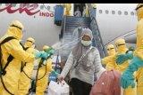 Petugas medis menyemprotkan cairan disinfektan pada Warga Negara Indonesia (WNI) dari Wuhan, China setibanya di Bandara Hang Nadim, Batam, Kepulauan Riau, Minggu (2/2/2020). Sebanyak 238 orang WNI dari Wuhan, China tersebut selanjutnya dipindahkan ke Natuna untuk menjalani observasi selama kurang lebih dua minggu guna memastikan kesehatannya dan terbebas dari virus corona. ANTARA FOTO/Kementerian Luar Negeri RI/nym