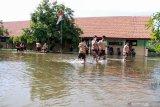 Siswa melintas di area sekolah yang tergenang air di SD Negeri Banjarasri, Tanggulangin, Sidoarjo, Jawa Timur, Jumat (7/2/2020). Menurut data BPBD Sidoarjo, sebanyak 350 rumah di Desa Kedungbanteng dan Desa Banjarasri terendam banjir selama hampir tiga minggu. Antara Jatim/Umarul Faruq/zk