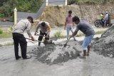 Polsek Depapre Papua dan warga kampung Waiya gotong-royong cor jalan berlubang