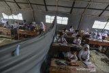 Siswa SD Negeri 3 Cigorowong mengikuti Kegiatan Belajar Mengajar (KBM) di bawah tenda BNPB di Desa Sukamukti, Kecamatan Cisayong, Kabupaten Tasikmalaya, Jawa Barat, Rabu (12/2/2020). Akibat empat ruang kelas mengalami kerusakan hingga ditopang tiang-tiang bambu sejak dua bulan lalu, kini siswa kelas I dan IV terpaksa belajarnya dipindahkan ke tenda darurat meskipun dalam kondisi panas dan kehujanan atas permintaan dari pemerintah daerah. ANTARA JABAR/Adeng Bustomi/agr