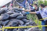 Petugas kepolisian memeriksa tumpukan kantong plastik sampah yang diduga berisi limbah medis di kawasan Palumbonsari, Karawang, Jawa Barat, Kamis (13/2/2020). Tumpukan sampah yang diduga limbah rumah sakit itu ditemukan di tempat pembuangan sampah sementara dan dipasangi garis polisi untuk proses penyelidikan lebih lanjut. ANTARA JABAR/M Ibnu Chazar/agr