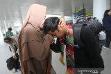 Muhammad Lutfi Madani (kiri) Warga Negara Indonesia (WNI) di sambut keluarganya usai menjalani masa karantina selama 14 hari di Natuna, Kepulauan Riau di terminal Bandara Internasional Syamsudin Noor, Banjarbaru, Kalimantan Selatan, Minggu (16/2/2020). Sebanyak tujuh WNI asal Kalsel tiba di Bandara Internasional Syamsudin Noor dan telah di terima keluarga masing-masing setelah dinyatakan sehat usai menjalani observasi selama 14 hari di Natuna, Kepulauan Riau. Foto Antaranews Kalsel/Bayu Pratama S.