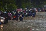Sejumlah pengendara mendorong motornya yang mogok saat menerjang genangan air di Jalan Soekarno-Hatta, Gedebage, Bandung, Jawa Barat, Senin (17/2/2020). Genangan air setinggi 50 hingga 100 sentimeter akibat hujan deras di beberapa wilayah Kota Bandung membuat Jalan Soekarno-Hatta di Gedebage tidak dapat dilalui oleh kendaraan kecil. ANTARA JABAR/Raisan Al Farisi/agr