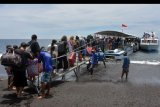 Warga dan wisatawan antre naik ke kapal cepat yang akan menuju pulau Nusa Penida menjelang Hari Raya Galungan di Pelabuhan Tribuana, Klungkung, Bali, Selasa (18/2/2020). Warga yang umumnya berasal dari pulau Nusa Penida dan Nusa Lembongan ramai mudik ke kampung halamannya untuk merayakan Hari Raya Galungan pada Rabu (19/2/2020). ANTARA FOTO/Nyoman Hendra Wibowo/nym