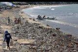 Nelayan dan warga beraktivitas di pantai yang dicemari sampah di Pantai Kedonganan, Badung, Bali, Jumat (21/2/2020). Sampah yang berasal dari daerah lain yang terbawa arus laut tersebut terdampar di beberapa kawasan pantai di selatan Bali. ANTARA FOTO/Nyoman Hendra Wibowo/nym.