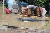 Warga menyelamatkan barangnya saat banjir di Desa Laden, Pamekasan, Jawa Timur, Minggu (23/2/2020). Hujan deras selama hampir enam jam pada hari Sabtu (22/2) menyebabkan sungai yang membelah kota kabupaten tersebut, meluap dan menggenangi ratusan pemukiman warga dengan ketinggian air hingga 160 cm. Antara Jatim/Saiful Bahri/zk